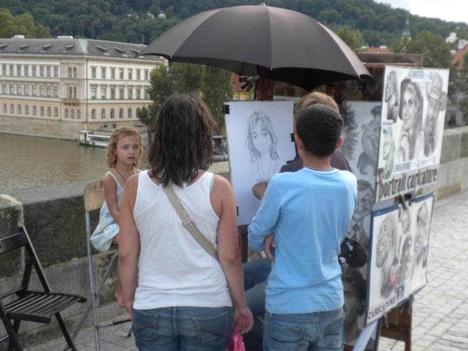Street artist on Charles Bridge, working on a caricature.