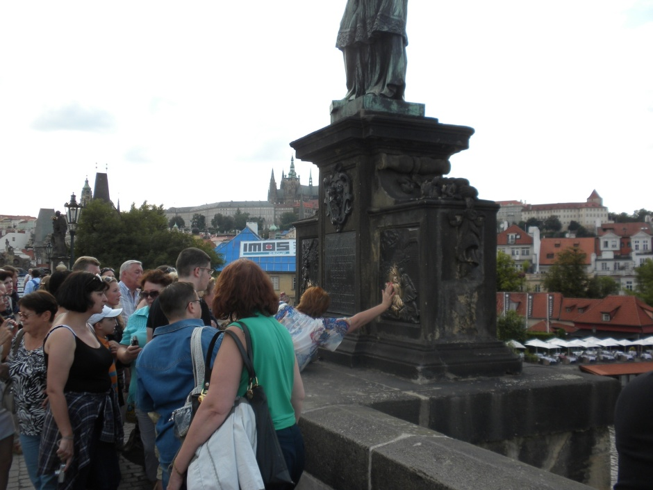 People rub the plaque on the statue of St. John Nepomuk on the bridge