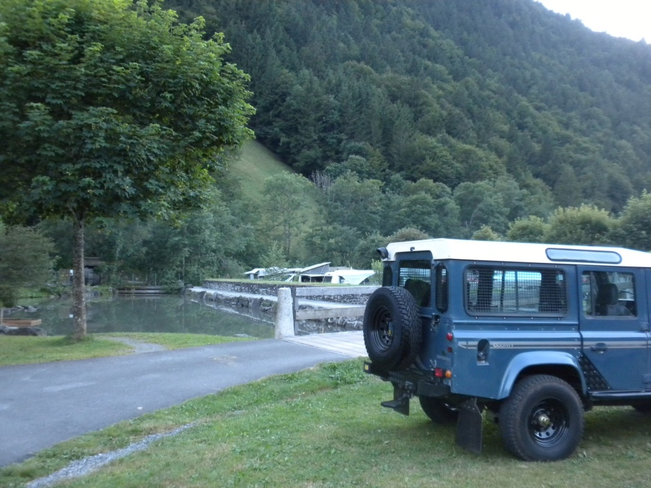 Defender at the campsite with the kids play pool behind