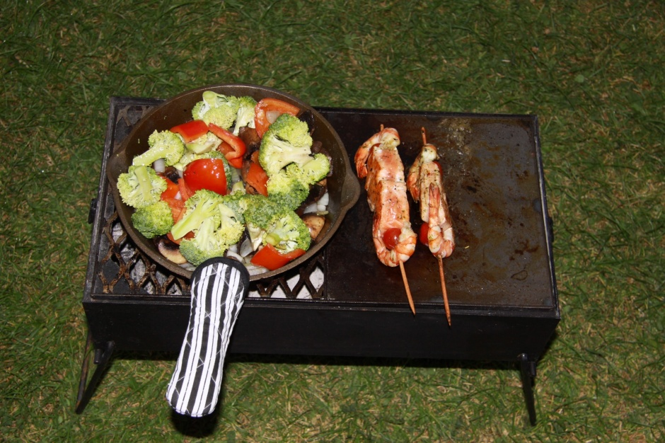 Stir-frying onions, mushrooms, peppers and broccoli whilst the salmon and shrimp kabobs are grilling - in the rain