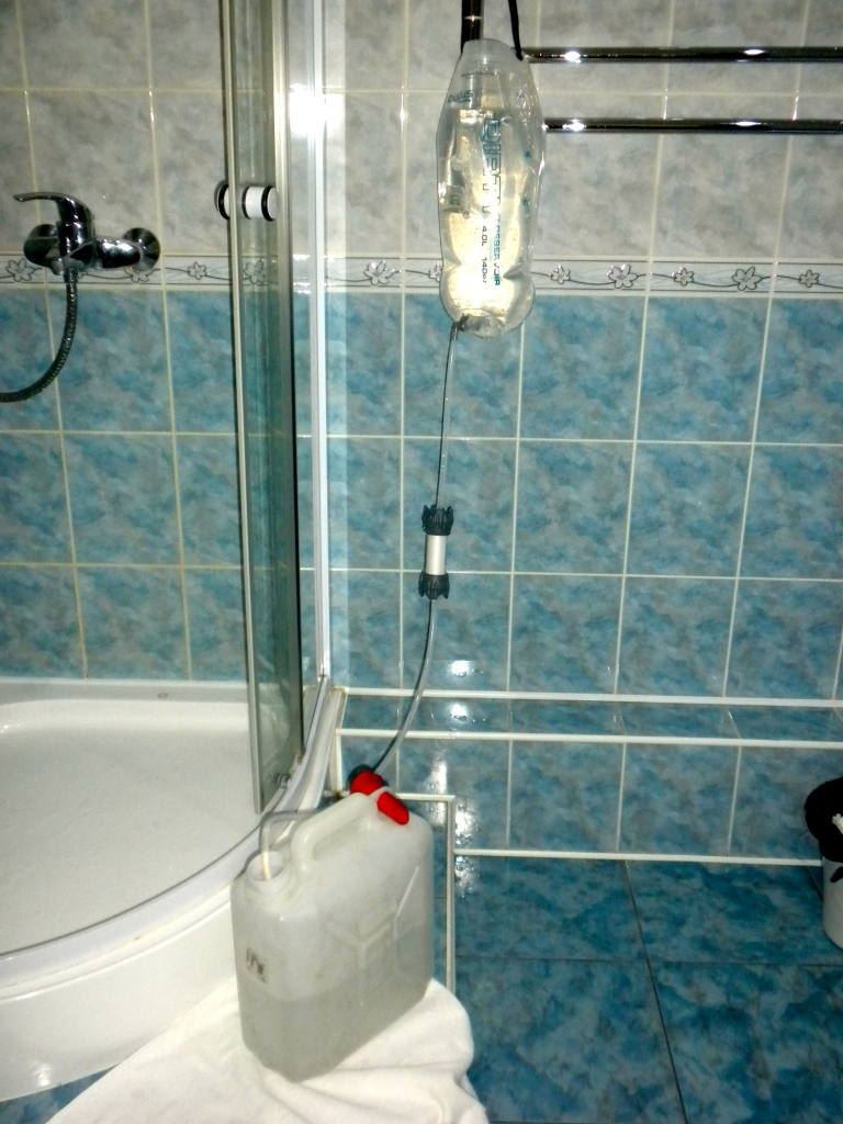 The bag of 'dirty water' is then hung up whilst gravity pushes it through the filter into the collection container.