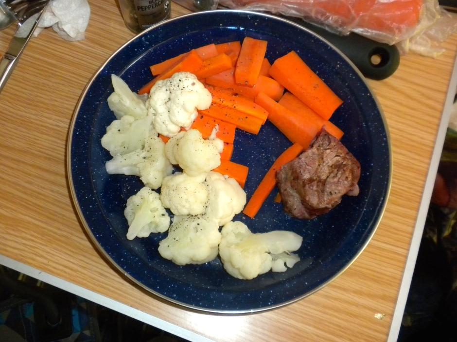 Tenderloin steak (partly eaten) and steamed veggies for dinner