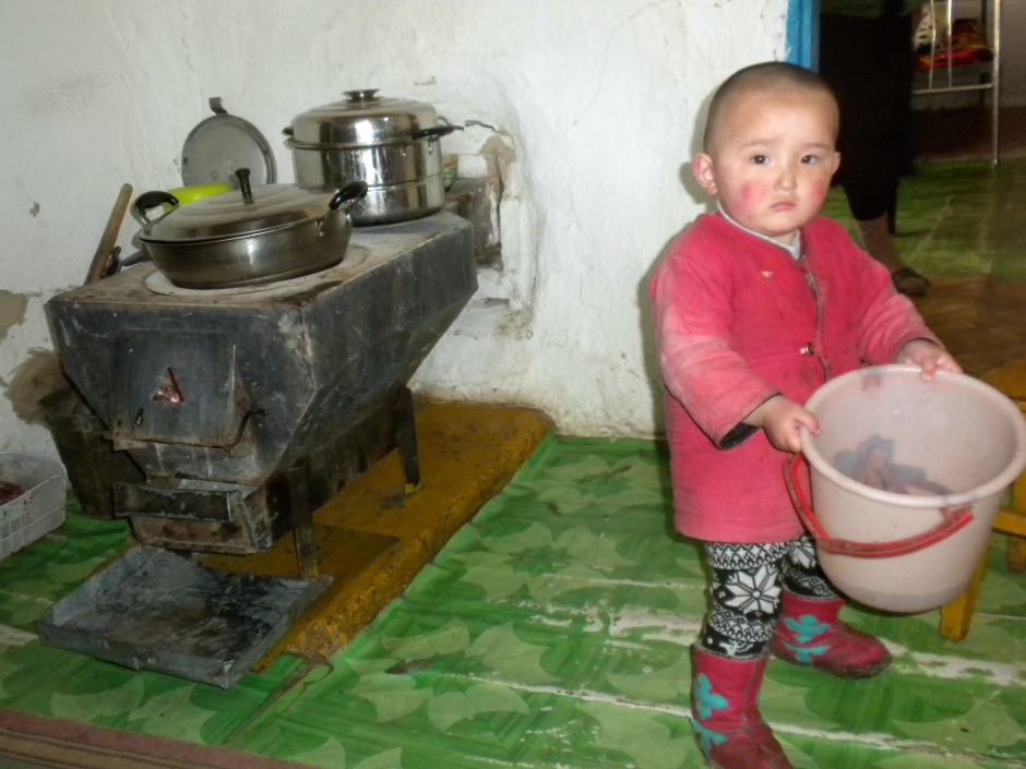 Cute Mongolian boy playing with a bucket of water