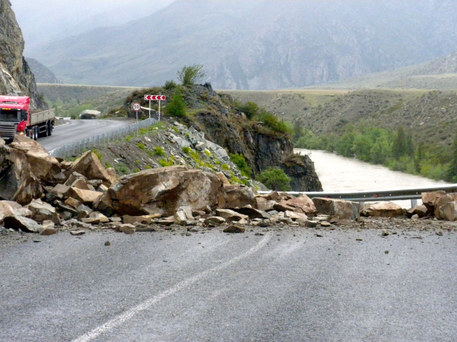 Rain brings down a rock-slide that partially blocks the road