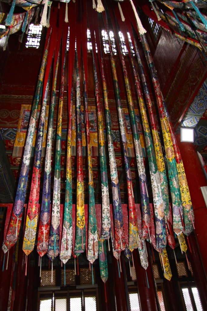 Colourful fabrics hanging from the ceiling inside the temple