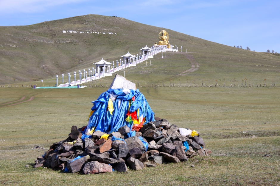 An ovoo (sacred pile of stones) with the steps leading to a buddha in the background