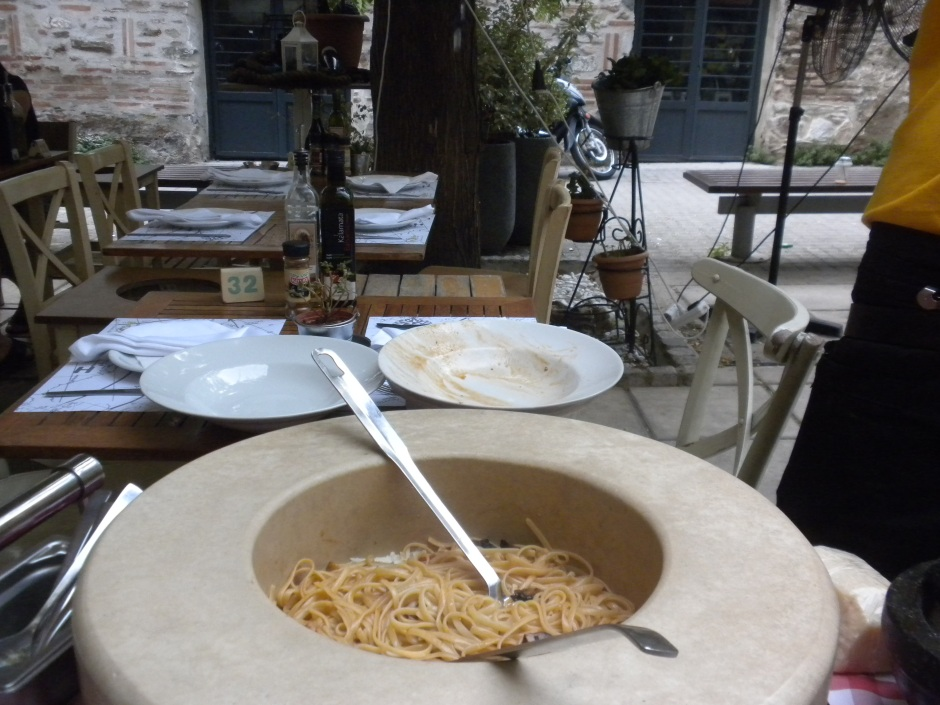 Cooked spaghetti is added to the parmesan cheese