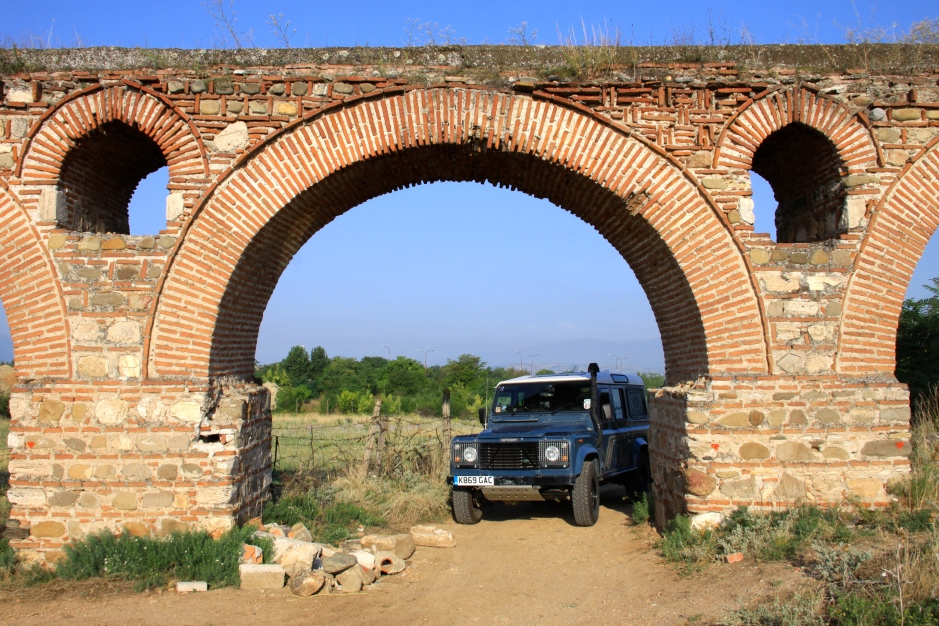 The Defender passes through one of the arches of the aqueduct.