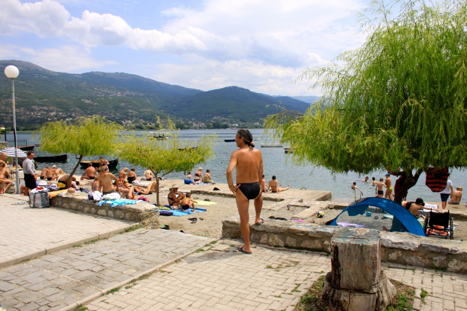 Concrete docks and gravel areas become makeshift beaches for sunbathing and swimming