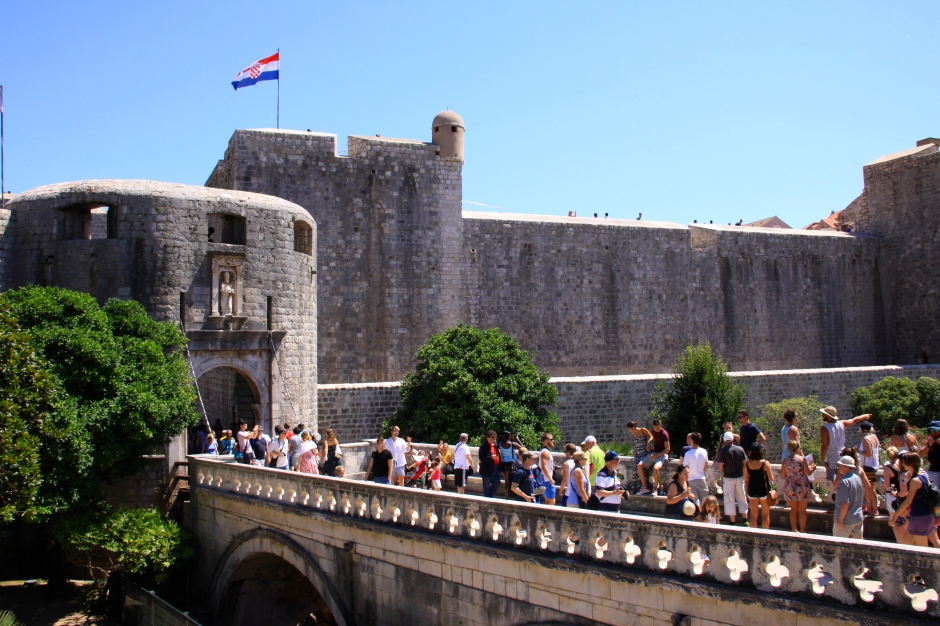 Crowds of tourists cross the bridge into the old town