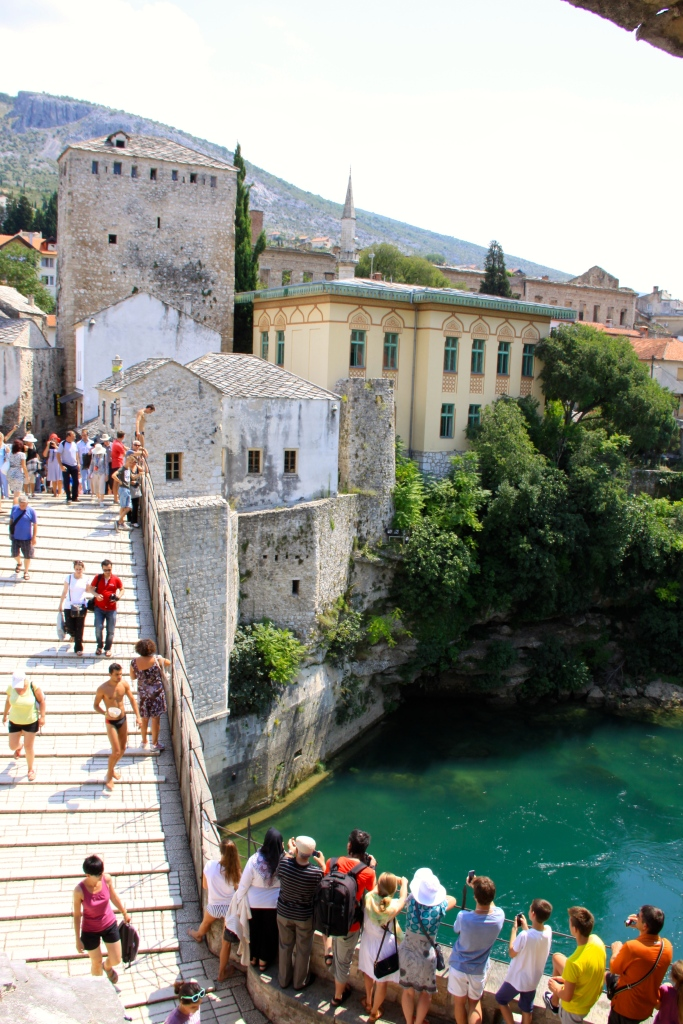 Tourists on the bridge watch for a diver to jump off
