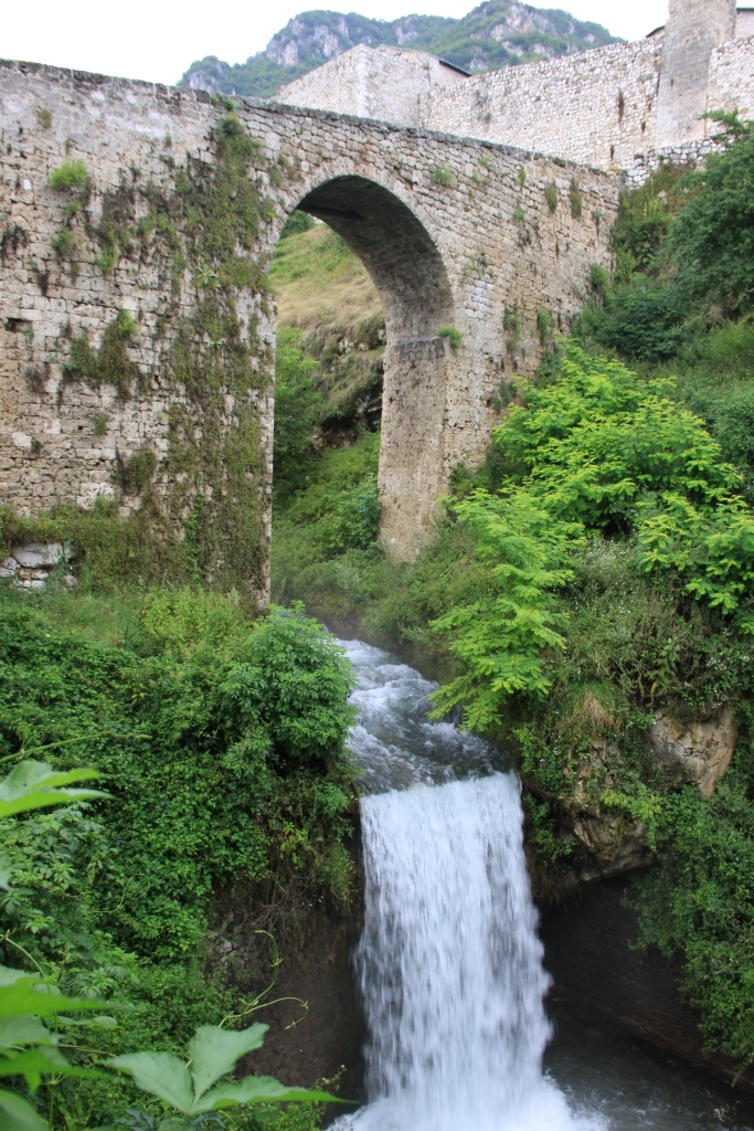 River runs through an arch and falls to a lower level