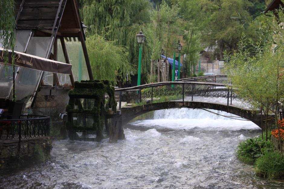 The river cascades under bridges and between restaurants
