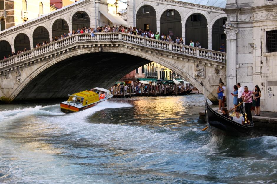 An ambulance speeds under the Rialto Bridge whilst a gondola rides its wake