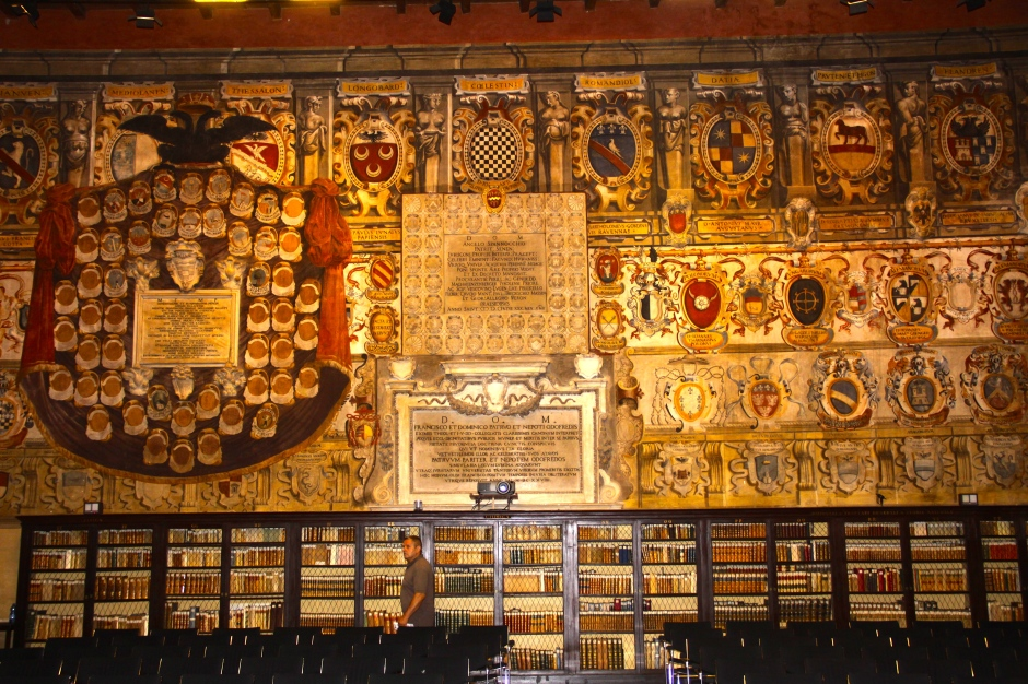 A wall of crests above bookshelves full of old reference books in the Mater Theatre