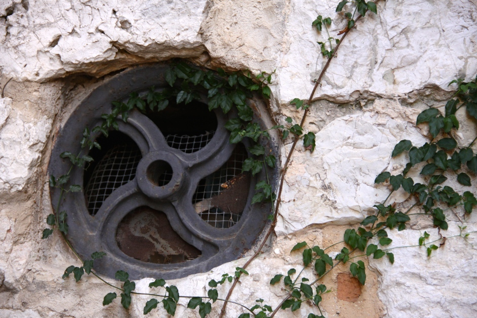 An old mechanical wheel or pulley that has been re-purposed to create a window
