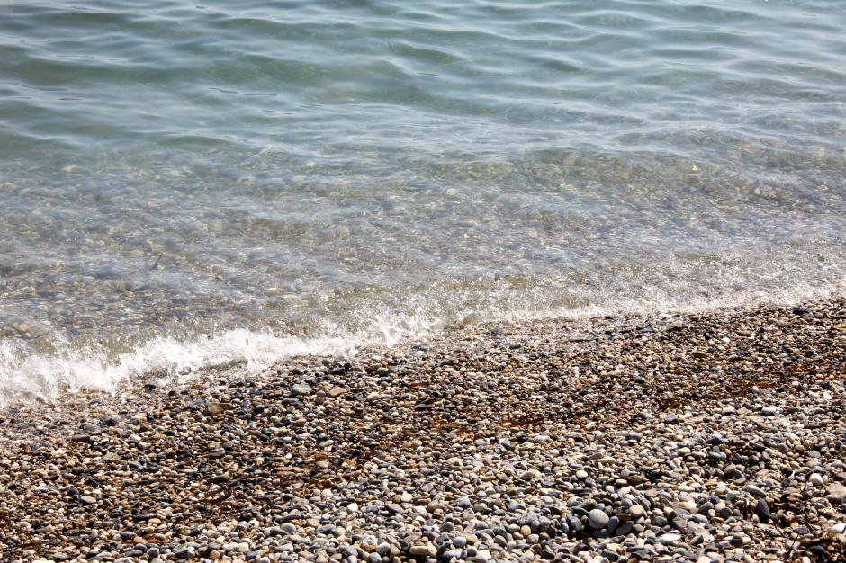The clear water of the Mediterranean lap against the pebbled beach outside the restaurant